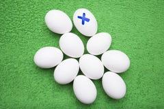Dez ovos brancos da galinha encontram-se em um fundo gramíneo-verde Imagem de Stock