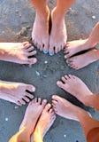 Dez pés de uma família na praia Foto de Stock