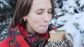 Deze video is over Close-up van het gezicht van een meisje dat hete thee of koffie in de winter op de straat drinkt, draagt zij g stock video
