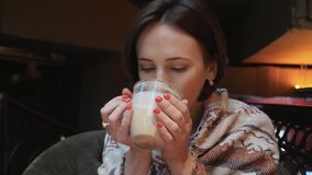 Deze video is over Jonge aantrekkelijke vrouw drinkt koffiethee in een restaurant Haar schouders zijn behandeld met warm gebreid  stock videobeelden