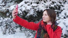 Deze video is over Mooi Jong Meisje in het sneeuwbos maakt een selfie Langzame Motie Portret van modieuze jonge mooie gi stock video