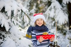 26. Dezember Der Junge Sankt-` s in Kappe und in einem Schal hält einen hellen Kasten mit einem Geschenk in der Hand Stockfotos