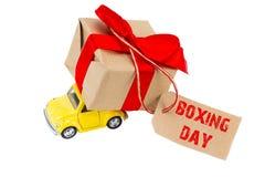 26. Dezember-Konzept Gelbes Retro- Spielzeugauto, das Geschenkkasten wi liefert Lizenzfreie Stockfotos