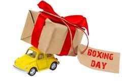 26. Dezember-Konzept Gelbes Retro- Spielzeugauto, das Geschenkkasten wi liefert Lizenzfreies Stockbild