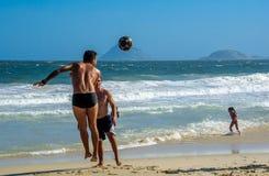 6. Dezember 2016 Springender Mann, der Strandfußball auf dem Hintergrund von Atlantik an Copacabana-Strand spielt Lizenzfreie Stockfotos