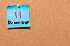 11. Dezember Tag 11 des Monats, Kalender auf KorkenAnschlagtafel Blume im Schnee Leerer Platz für Text Lizenzfreie Stockfotografie