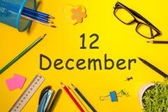 12. Dezember Tag 12 von Dezember-Monat Kalender auf gelbem Geschäftsmannarbeitsplatzhintergrund Blume im Schnee Lizenzfreie Stockfotos