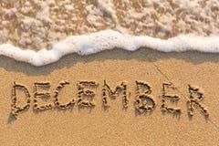 Dezember - Wort gezeichnet auf den Sandstrand mit der weichen Welle Lizenzfreies Stockfoto