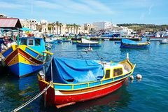 Dghajsa fishing boats in Marsaxlokk harbour. Traditional Maltese Dghajsa fishing boats in the harbour with waterfront buildings to the rear, Marsaxlokk, Malta Stock Photography