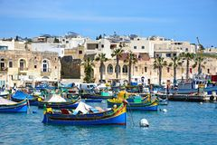 Dghajsa fishing boats moored in Marsaxlokk harbour, Malta. Traditional Maltese Dghajsa fishing boats in the harbour with waterfront buildings to the rear Royalty Free Stock Image