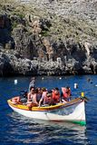 Dghajsa water taxi full of tourists, Blue Grotto. Tourists in traditional Dghajsa water taxi boats at the departure point in the bay, Blue Grotto, Malta, Europe Royalty Free Stock Photos