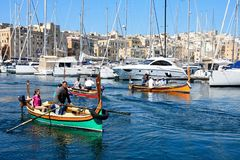 Dghajsa water taxi in the marina, Vittoriosa. Passengers on board traditional Maltese Dghajsa water taxis in the harbour with views towards Senglea waterfront Royalty Free Stock Images