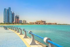 Corniche Abu Dhabi. Dhabi skyline in the blue sky from Corniche in Abu Dhabi, United Arab Emirates, Middle East. Modern skyscrapers and landmark on background Stock Photography