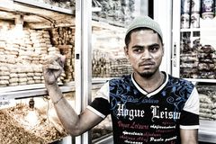 Dhaka, Bangladesch, am 24. Februar 2017: Hübscher junger Verkäufer, der in seinem Shop in Dhaka aufwirft Lizenzfreie Stockfotografie