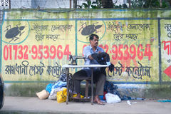 Dhaka, bangladesh, august 2017- a man sewing and tailoring at street footh path against wall located at motijhil in Stock Image