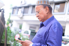 Dhaka, bangladesh, august 2017-a old man with cap holding smart phone in hand at street located at dhaka in banlgadesh Royalty Free Stock Photo