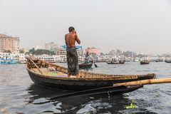 Dhaka, Bangladesh: Boatman was zelf op een houten boot onderaan de Rivier van Buriganga Ganmges in Oude Dhaka Grote witte veerboo Royalty-vrije Stock Foto