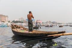 Dhaka, Bangladesh: Boatman washing himself on a wooden boat down Buriganga Ganmges River in Old Dhaka. Large white ferry Royalty Free Stock Photo