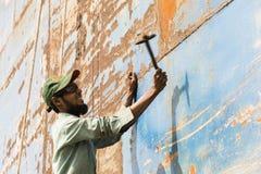 Dhaka, Bangladesh, February 24 2017: A worker at a shipyard in Dhaka Bangladesh beats the rust from the hull with a hammer. Dhaka, Bangladesh, February 24 2017 stock photos