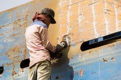 Dhaka, Bangladesh, o 24 de fevereiro de 2017: Trabalhador em uma doca do navio em Dhaka que mói uma placa Fotografia de Stock