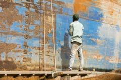 Dhaka, Bangladesh, o 24 de fevereiro de 2017: Um trabalhador em um estaleiro em Dhaka bate a oxidação da casca Fotos de Stock