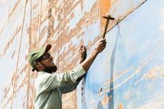 Dhaka, Bangladesh, o 24 de fevereiro de 2017: Um trabalhador em um estaleiro em Dhaka bate a oxidação da casca Imagem de Stock