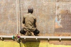 Dhaka, Bangladesh, o 24 de fevereiro de 2017: Um trabalhador em um estaleiro em Dhaka Bangladesh senta-se em uma placa de madeira Imagem de Stock