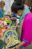 Art institute student painting a colorful mask. Dhaka, Bangladesh. 12th Apr, 2016. Dhaka University Fine Arts FFA student paints a mural to celebrate upcoming stock image