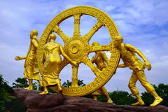 Dhamma金黄轮子在天空云彩的 免版税库存图片
