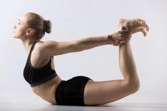 Dhanurasana, Bow Pose. Sporty beautiful young woman practicing yoga, doing Dhanurasana, Bow Pose, working out wearing black sportswear, studio Royalty Free Stock Image