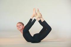 Dhanurasana yoga. Little girl doing yoga on white background Royalty Free Stock Photos