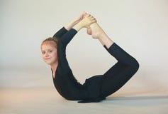 Dhanurasana yoga. Little girl doing yoga on white background Royalty Free Stock Photo