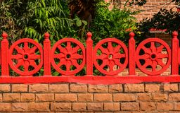 Dharma Wheel Buddhist symbol. In old fence of local temple stock photos
