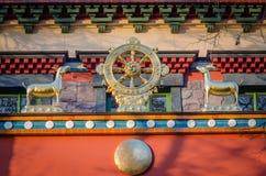 Dharmacakra - Rad des Dharma und des zwei Damhirschkuh simbol von Buddhismus, Hinduismus, Jainismus Lizenzfreie Stockfotos
