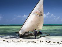 Dhau sailboat, white sail in the wind, white beach, emerald sea royalty free stock photography