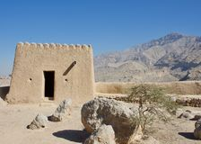 Dhayah Fort in Ras al Khaimah in the sunshine with Hajar Mountains in background. royalty free stock photos