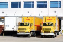DHL lastbilar och släp som parkeras på ett lager arkivbild