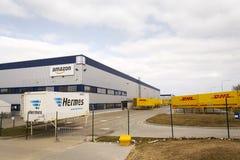 DHL och Hermes sändningsbehållare framme av amasonlogistikbyggnad på mars 12, 2017 i Dobroviz, Tjeckien Royaltyfria Bilder