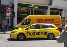 DHL-Packwagen und -taxi auf der Straße Lizenzfreies Stockfoto