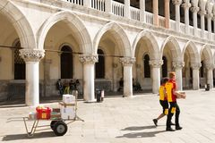 DHL Postmen delivering parcels on the Piazza San Marco in Venice. Venice, Italy - September 29, 2017: Two DHL postmen delivering parcels on the Piazza San Marco stock images