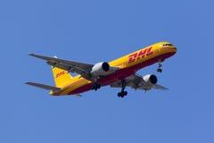 DHL 757 su chiaro cielo blu Fotografia Stock