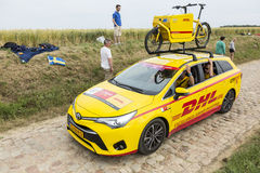 DHL Vehicle on a Cobblestone Road- Tour de France 2015. Quievy,France - July 07, 2015: DHLvehicle during the passing of the Publicity Caravan on a cobblestoned royalty free stock photography