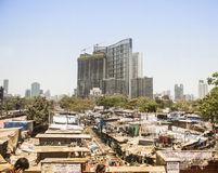 Dhobi Ghat laundry, Mumbai, India. Dhobi Ghat open air laundry in shadow of high rise buildings and skyline of Mumbai, India on sunny day Stock Image