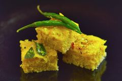 Dhokla Indian dish with chili on a black background. Close view of Dhokla Indian dish with chili on a black background Royalty Free Stock Photo