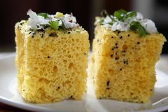 Dhokla, Steamed cake. Dhokla is a traditional Gujarati snack that is served for festive meals. Rice and Urad dal are the main ingredients. Although dhoklas taste stock photography