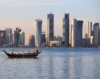 Dhow and Doha skyline. A dhow returns to harbour in Doha, Qatar, at sunset, with the city's modern skyline in the background Stock Photography