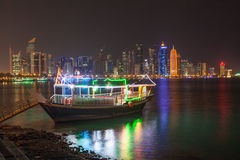 Dhow and Doha skyline at night Stock Photo