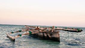 Dhow eller mokoro i det grunda havsvattnet på den Jamibiani stranden, Zanzibar royaltyfri foto