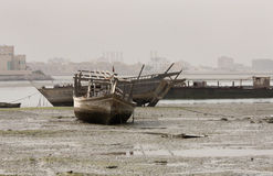 Dhow, fishing boat lying on sea bed in low tide Stock Photos