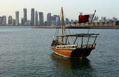 Dhow with flag and skyline. Arabian shuw'i dhow flying the Qatari flag in Doha bay, with the capital city's new skyline behind it Royalty Free Stock Photography